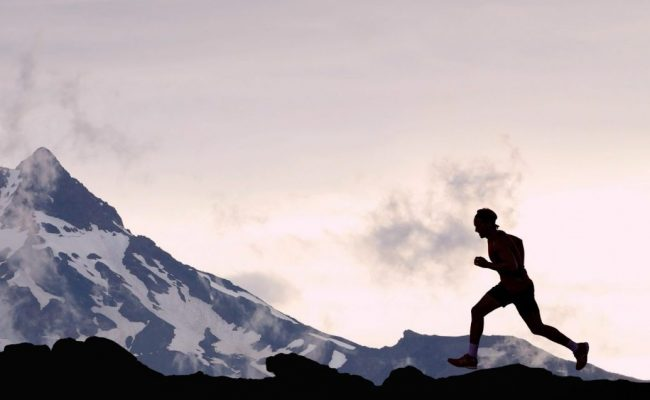 Running man athlete trail running in mountain summit background. Man on run training outdoors active fit lifestyle. Silhouette at sunset.